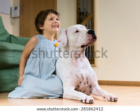 smiling female toddler on the floor with dogo Argentino