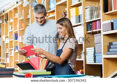 Smiling female worker and male customer holding greeting card in shop - stock photo