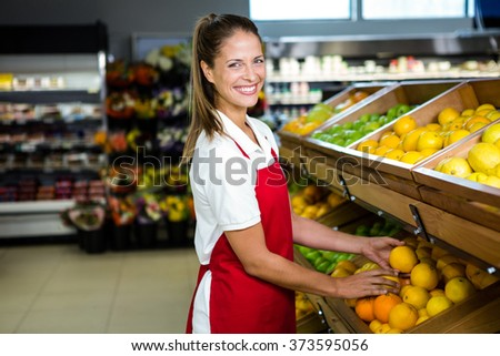 Smiling female worker stocking lemons in grocery store - stock photo