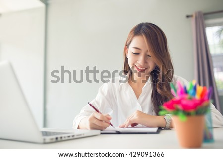 Smiling female writing on notebook