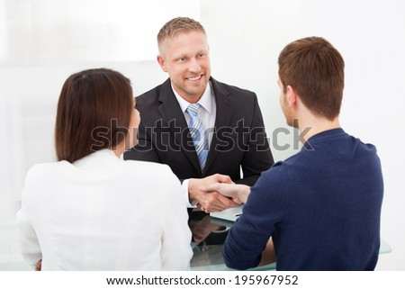 Smiling financial advisor shaking hand with young couple at office desk - stock photo