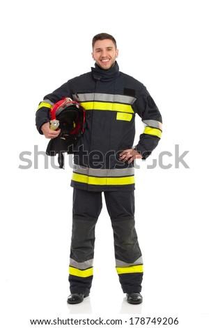 Smiling firefighter holding red helmet under his arm. Full length studio shot isolated on white. - stock photo