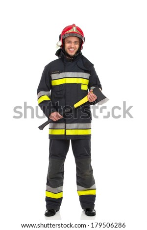 Smiling firefighter posing and holding axe, Front view. Full length studio shot isolated on white. - stock photo