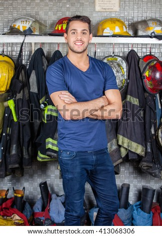 Smiling Firefighter Standing At Fire Station - stock photo