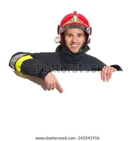 Smiling fireman in red helmet standing behind placard and pointing. Head and shoulders studio shot isolated on white. - stock photo