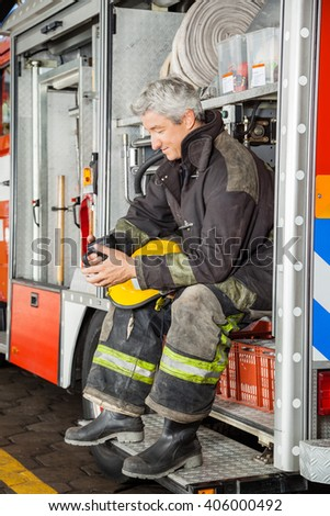 Smiling Fireman Looking At Coffee Mug While In Truck - stock photo