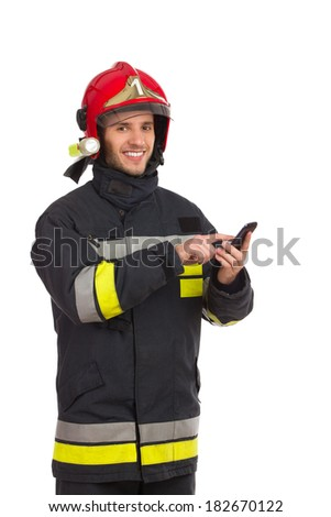 Smiling fireman using smart phone and looking at camera. Three quarter length studio shot isolated on white. - stock photo