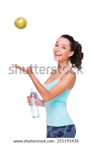 Smiling fit woman holding a bottle of water and throwing up an apple, isolated on white background - stock photo