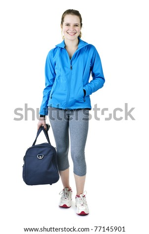 Smiling fit young woman with gym bag standing ready for fitness exercise - stock photo