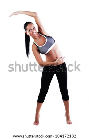 Smiling fitness woman making stretching exercises isolated on white - stock photo