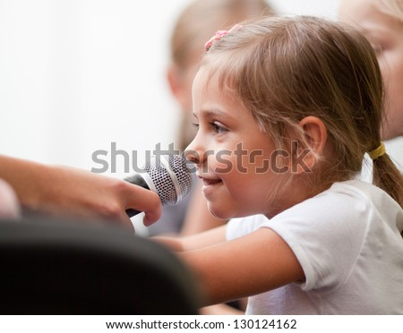 Smiling five year old girl speaks into handheld microphone. A woman's hand holds a microphone in front of her - stock photo