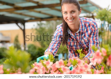 Smiling florist working in garden center looking at camera - stock photo