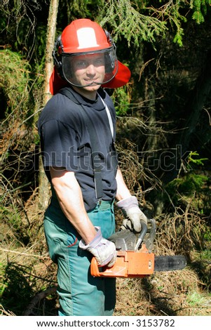 Smiling forestry worker with a chainsaw - stock photo
