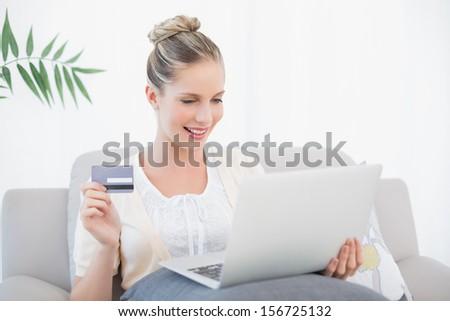 Smiling fresh model shopping online using laptop sitting on cosy sofa - stock photo