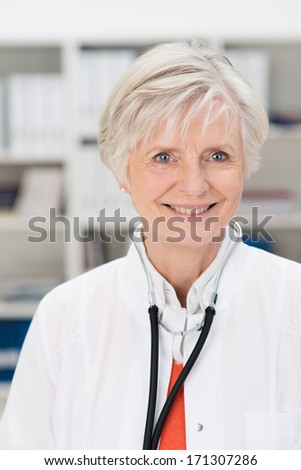 Smiling friendly attractive mature female doctor or General Practitioner standing in her office or surgery with shelves of files in the background - stock photo