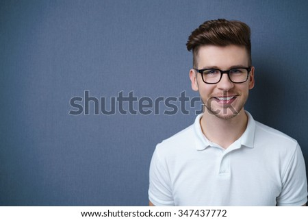 Smiling friendly attractive young man with a modern trendy hairstyle posing against a dark grey background with copyspace, head and shoulders portrait - stock photo