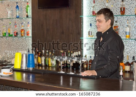 Smiling friendly barman serving alcoholic cocktails standing behind the bar counter with three cocktail glasses full of an exotic blend in front of him - stock photo