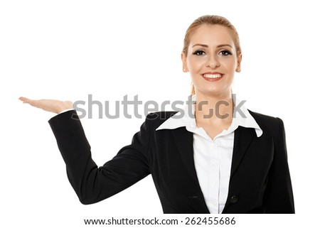 Smiling friendly businesswoman presenting an imaginary product, to the copyspace - stock photo
