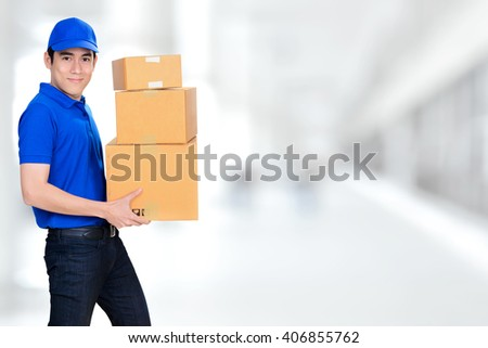 Smiling friendly delivery man carrying parcel boxes on blur white background - stock photo
