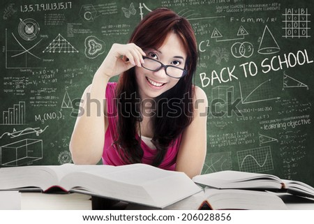 Smiling friendly female college student with textbooks.