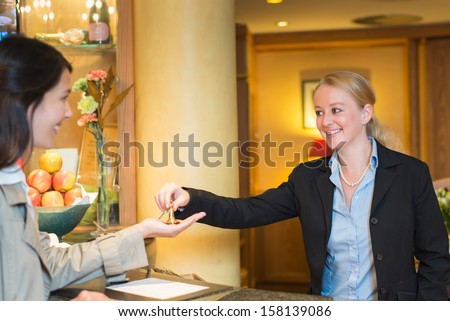 Smiling friendly hotel receptionist standing behind the service desk in a hotel lobby booking in a female client handing her the room keys for her stay during her vacation - stock photo