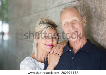 Smiling friendly middle-aged couple posing together alongside a wall looking at the camera - stock photo