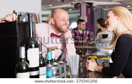Smiling friends drinking and chatting with cheerful barman at bar counter - stock photo