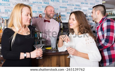 Smiling friends drinking and chatting with young barman at bar counter - stock photo