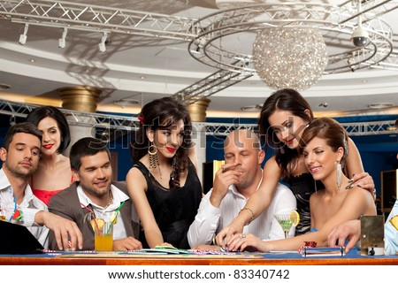 smiling friends enjoying a gambling night - stock photo