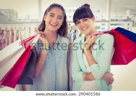 Smiling friends holding shopping bags in clothes store - stock photo