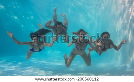 Smiling friends looking at camera underwater in swimming pool on their holidays - stock photo