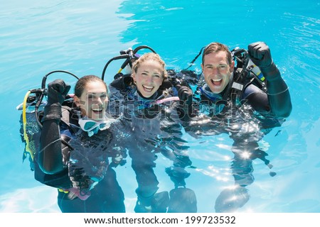 Smiling friends on scuba training in swimming pool cheering at camera on a sunny day - stock photo