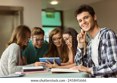 Smiling friends sitting studying and using tablet pc after school for teamwork - stock photo