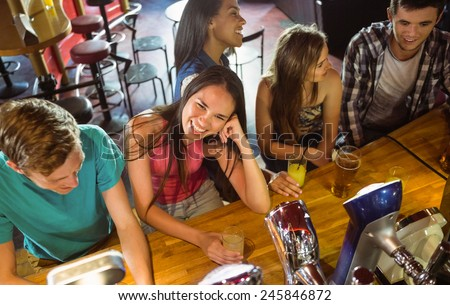 Smiling friends talking and drinking beer and mixed drink in a bar - stock photo