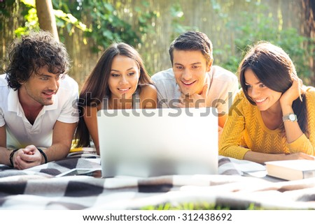 Smiling friends using laptop outdoors - stock photo
