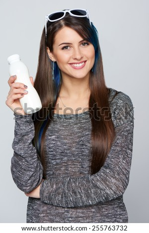 Smiling funky woman holding a bottle of dairy produce over gray background - stock photo
