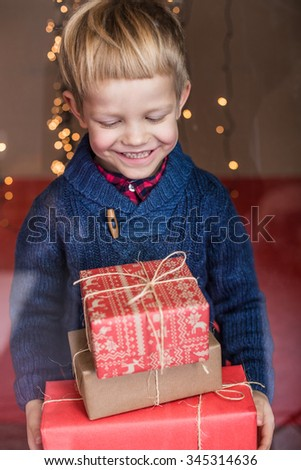 Smiling funny child holding Christmas gift in hand. Christmas concept. Birthday - stock photo