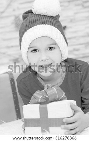 Smiling funny child in Santa red hat holding Christmas gift in hand  ( black and white ) - stock photo