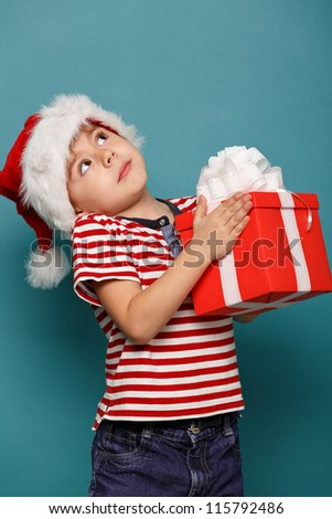 Smiling  funny child in Santa red hat holding Christmas gift in hand. Christmas concept. - stock photo