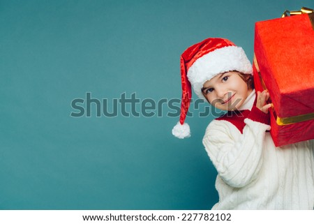 Smiling funny child (kid, boy) in Santa red hat. Holding Christmas gift in hand. Christmas concept. Shooting on blue background - stock photo