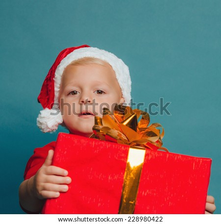 Smiling funny child (kid, boy) in Santa red hat holding Christmas gift in hand. Christmas concept. - stock photo