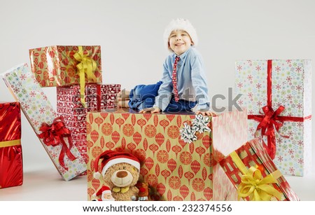 Smiling funny child with big gifts - stock photo