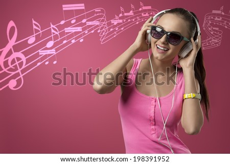 smiling funny girl listening music with headphones and posing with pink singlet and long brown ponytail  - stock photo