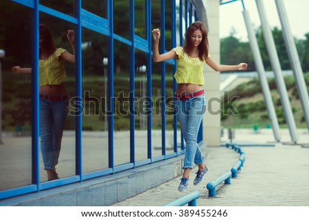 Smiling funny hipster girl in blue jeans running and jumping in the summer city. Modern youth lifestyle concept. Outdoor shot - stock photo