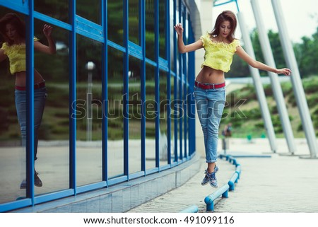 Smiling funny hipster girl in blue jeans running and jumping in the summer city. Modern youth lifestyle concept. Outdoor shot