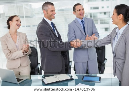 Smiling future workmates shaking hands in bright office - stock photo