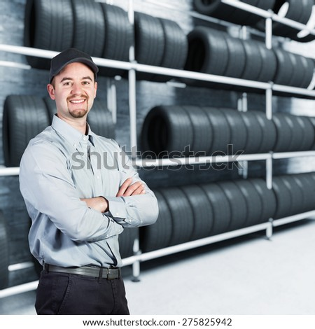 smiling garage man and tires background - stock photo