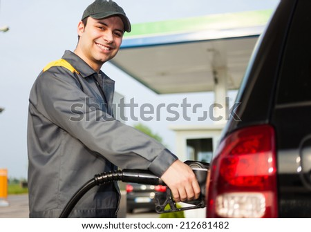 Smiling gas station attendant at work - stock photo