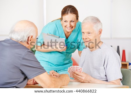 Smiling geriatric nurse watching twi old men playying cards in a nursing home - stock photo
