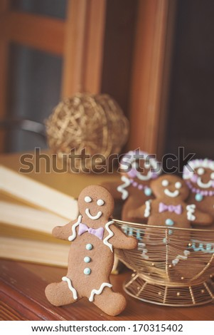 Smiling gingerbread man standing next to open book. Closeup with shallow dof. Copy space included for text. - stock photo